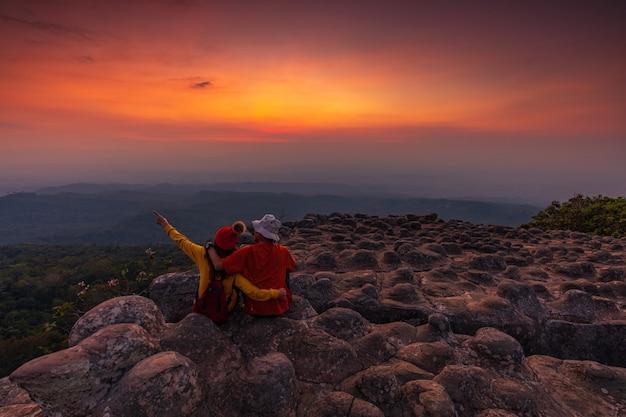 Молодая пара сидит на скале в горах