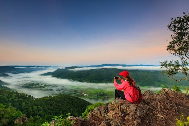 Девушка в красной куртке стоит на горе