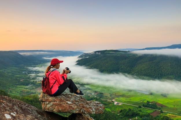 Девушка в куртке стоит на горе