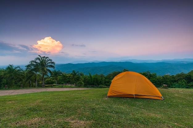 Оранжевая палатка на скале вечером.