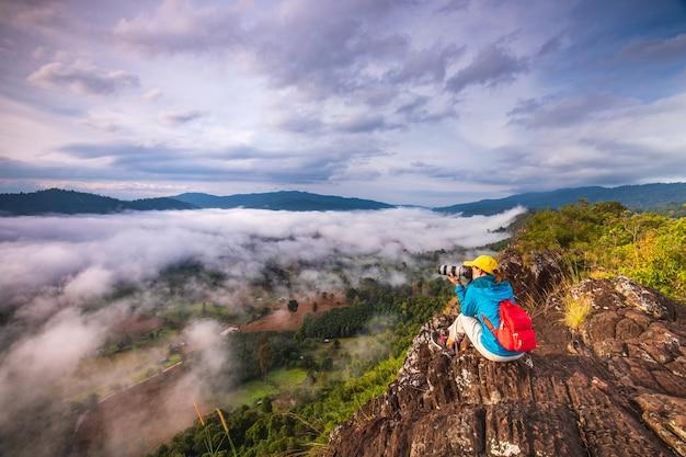 若い女の子は、高山の霧の海の写真を撮っています。