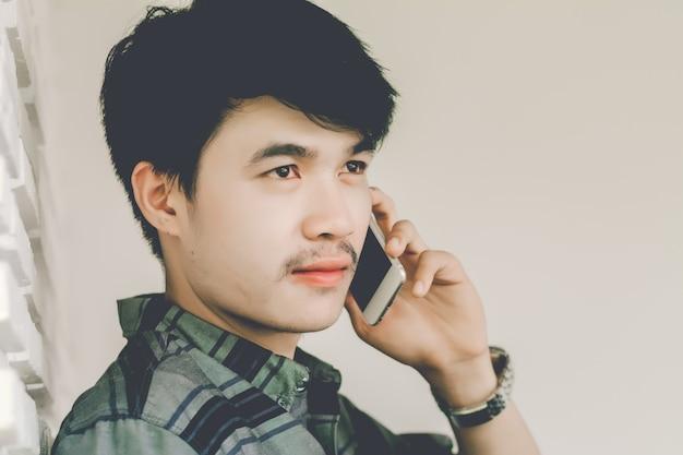 Молодой человек звонит с мобильного телефона, а один в кафе в свободное время.