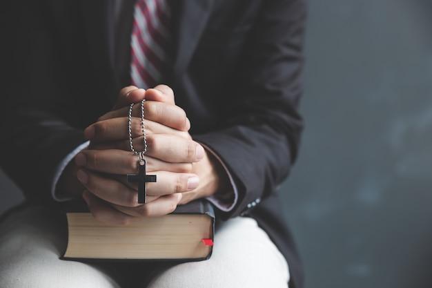 祈る若い男と聖書の机の手