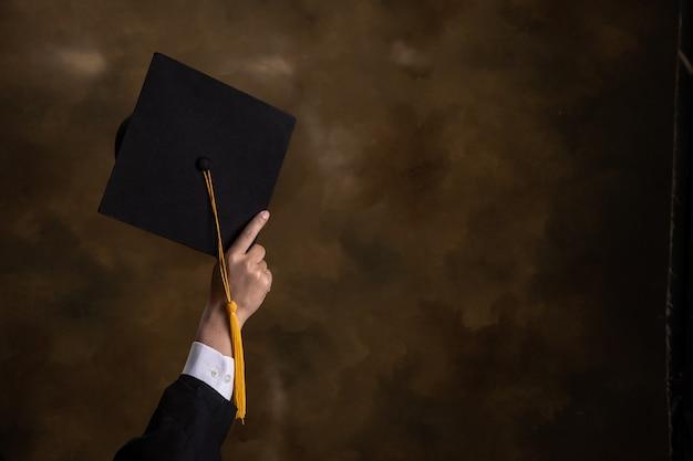 Деловой человек держит выпускной шляпу