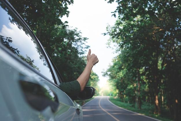 田舎で運転している間、彼の手を通して風を感じる男性ドライバー。
