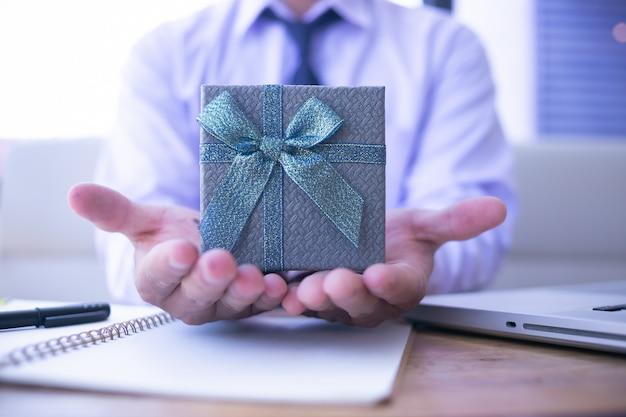 Коробка подарка бизнесмена с днем рождения от клиента в офисе.