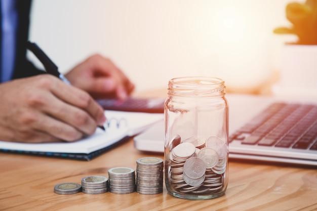 コインとビジネスの男性は、コストと金融を書きます。お金の概念を保存します。