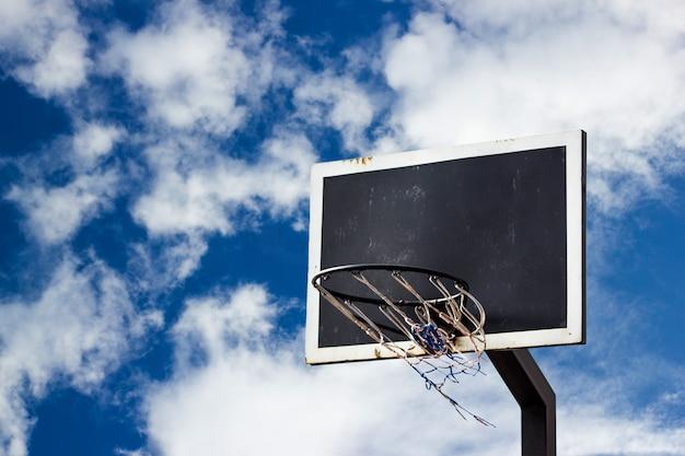 青い空にストリートバスケットボールボードの背景