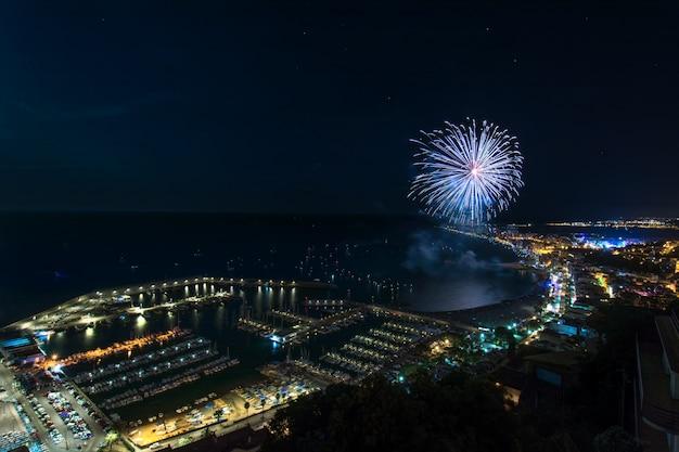 Потрясающий широкоугольный снимок фейерверка над бланесом в каталонии, испания