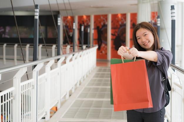 色付きバッグで買い物に幸せなアジアの女の子の肖像画。