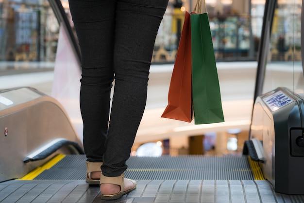 ショッピングモールで赤と緑の買い物袋を保持している女性のクローズアップ。