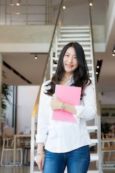 白いシャツと成功したビジネスの概念の階段の前に立っているピンクの本を持ってブルージーンズを身に着けているスマートな若いビジネス女性