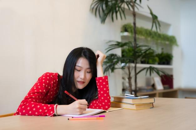 ノートにメモを取る女子学生のクローズアップ。