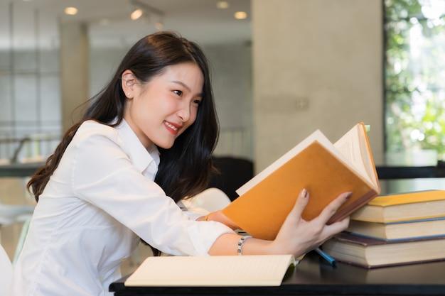 図書館のテーブルでノートと本を研究する白いシャツを着て美しい学生