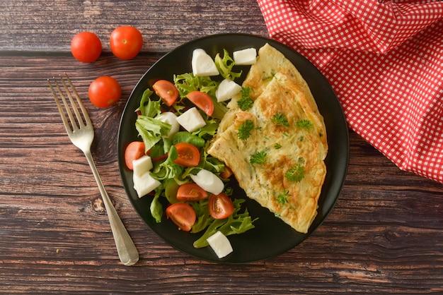 チェリートマト、モッツァレラチーズ、グリーンサラダの卵のオムレツ。コピースペースを持つ木製のテーブル。