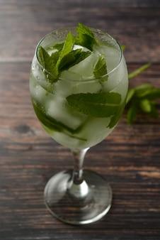 ワイングラスで夏のカクテルを飲みます。ミントの葉、ジントニック、シロップでさわやかなドリンク。 。