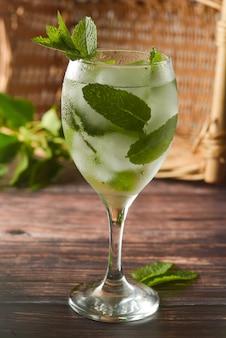 ワイングラスで夏のカクテルを飲みます。ミントの葉、ジントニック、シロップと爽やかなドリンク。 。