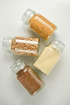 無駄のないコンセプトガラス瓶の中の様々な生の穀物。