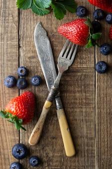 ミックスベリー、ブルーベリー、ヴィンテージの木製の背景にイチゴスタイルのフォークとナイフ。スタイルの食べ物