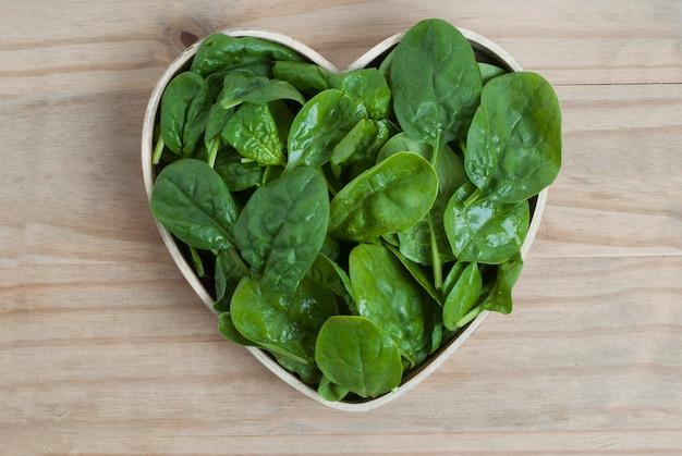 Изолированные листья шпината, деревянная плита в форме сердца.