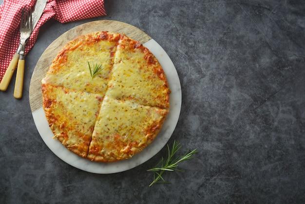 暗いテーブルの上の厚い地殻とチーズのおいしい自家製ピザ