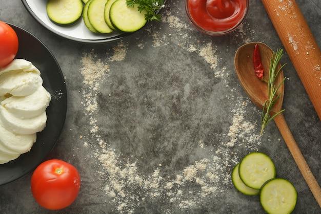 Круглая рамка из муки, скалки и овощей. копировать пространство