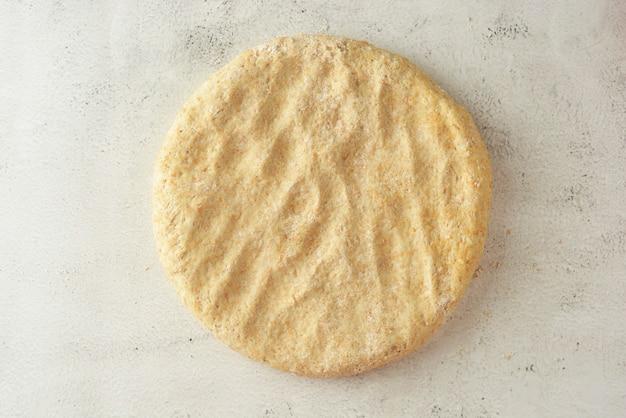 Сырое круговое тесто. кондитерское или хлебное тесто. яркий фон