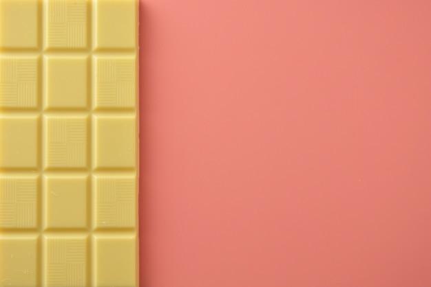 ピンクの上に分離されたホワイトチョコレート
