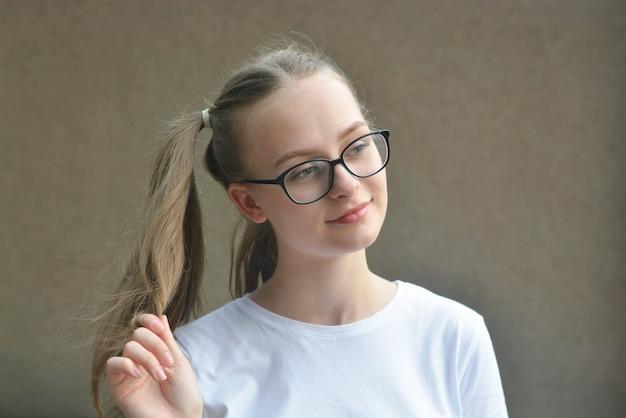 陽気なポジティブなかわいい子供、十代の少女、気分が良く、笑顔と長い髪の尾を見せています。