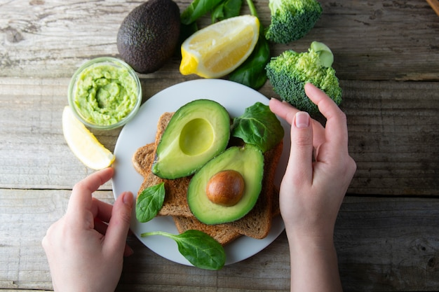 アボカドトーストサンドイッチ、有機食品。女性の手が健康的な食品を調理します。