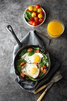 焼きたてのトマトを添えたフライパンで目玉焼き、ヘルシーな朝食、