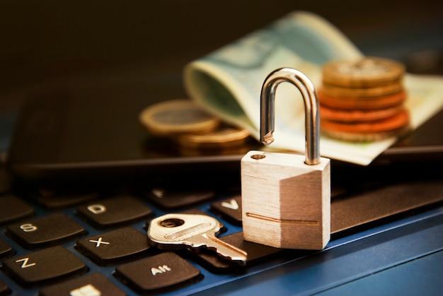 オンラインショッピング 。ラップトップ上のお金の横にあるラップトップの南京錠。安全でないオンラインショッピングの概念。