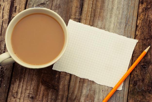 空の空白ページ紙と木製のテーブルの上のコーヒーカップ。テキストを追加する準備ができました。レトロなフィルター。平干し。