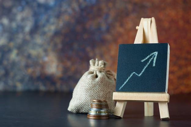 金融お金の袋と描かれたグラフ。給与または収入の増加。コピースペース