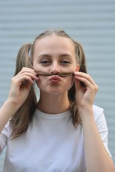 Весело подросткового возраста девочка, улыбаясь и делая усы с прядь волос.