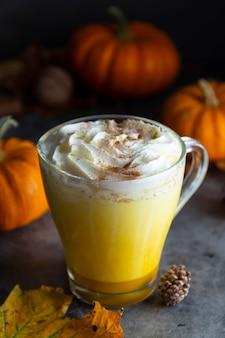 香辛料入りのゴールデンミルクカボチャの秋のラテドリンクミルクセーキとクリームの泡