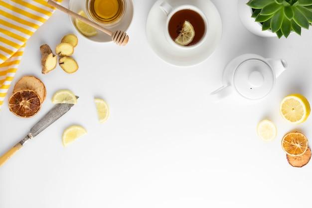 白い背景の上のレモン蜂蜜暑い秋とジンジャーティー