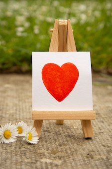赤いハート、手は白いステッカーに水彩の心を描く。愛の概念。