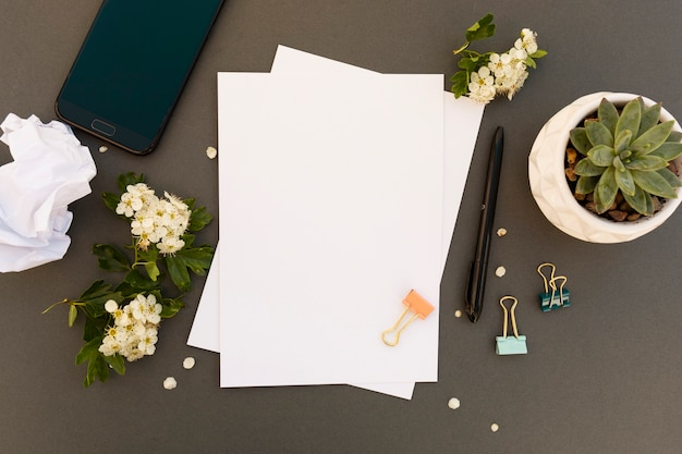 仕事机、テーブルは、スマートフォン、空白の紙、春の花のフレームとモックアップします。オフィスワークテーブルスペースをコピーします。