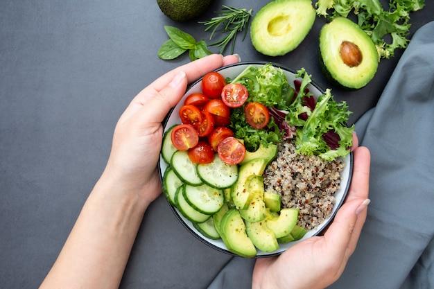 Здоровая пища. женская рука держа чашу будха с киноа, авокадо, огурец, салат, помидоры, оливковое масло.