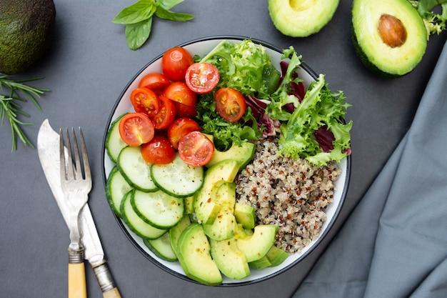 Здоровая пища. чаша будда с киноа, авокадо, огурец, салат, помидоры, оливковое масло.