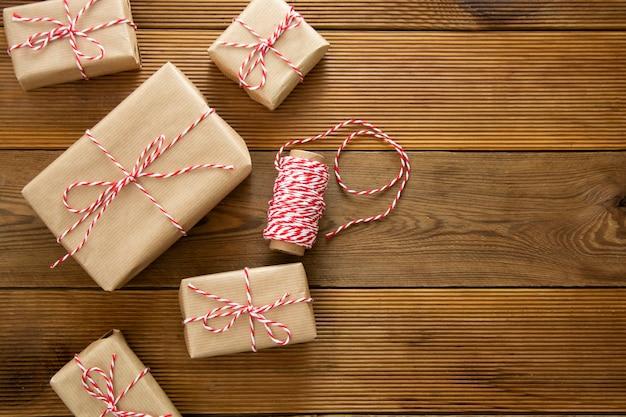 Рождественский фон подарочные коробки, завернутые в крафт-бумаги на деревянных фоне. вид сверху, деревенский стиль. копировать пространство