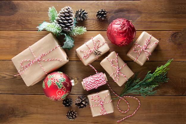 Рождественский фон подарочные коробки крафт-бумаги с сосновыми шишками, еловыми отрубями, красными шарами на коричневом деревянном столе с пространством копии. рождество плоская планировка, копия пространства.