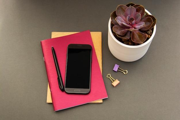 ピンクのノート、スマートフォン、多肉植物とフラットレイアウトモダンなミニマルワークスペースデスク。女性用デスク