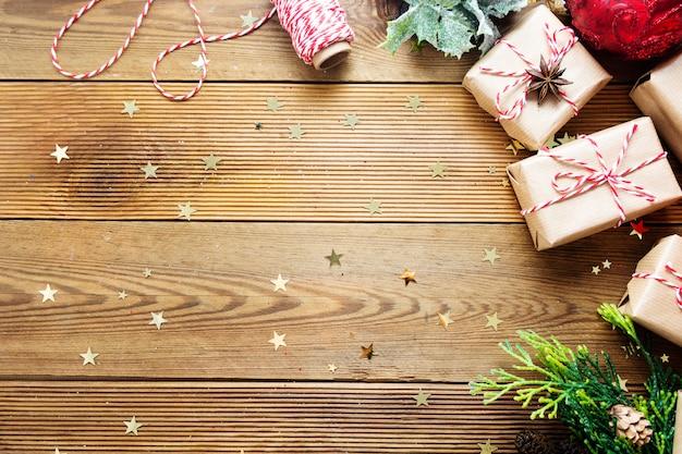モミの枝、赤いつまらないもの、松ぼっくりのクラフトペーパーに包まれたクリスマスギフトボックス。