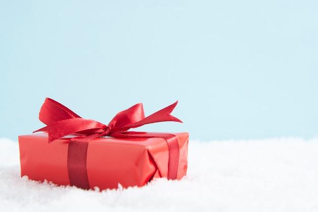 雪、コピースペースに赤の弓とクリスマスの赤いギフトボックス。