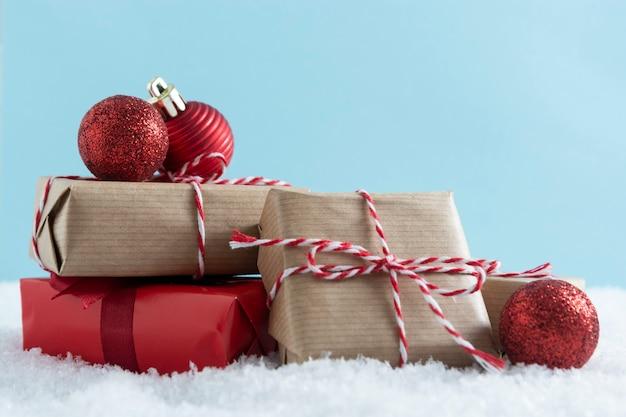 雪の上の赤いつまらないクリスマス赤とクラフトギフトボックス。