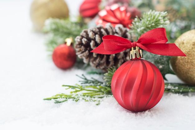 Рождественский фон с безделушками, зелеными еловыми ветками, сосновыми шишками, на белом фоне снега.