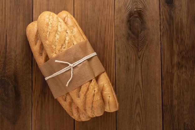 Хлеб булочки багеты на деревянный стол