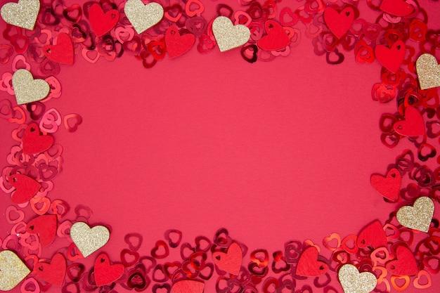 抽象的なフレーム、ボーダー、赤の背景に金色のハート形のキラキラ。バレンタインデーのフラット。